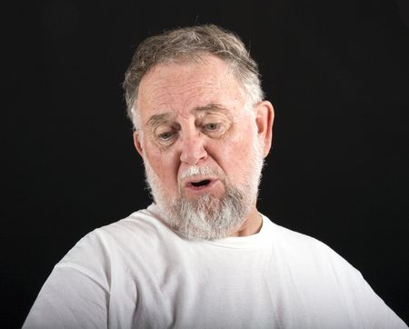 woe: An old man in a white tshirt against a black background with an expression of woe or sadness Stock Photo