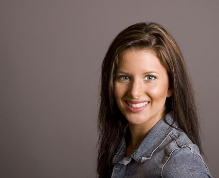 A  brown haired woman smiling at camera in a denim jacket against a grey background
