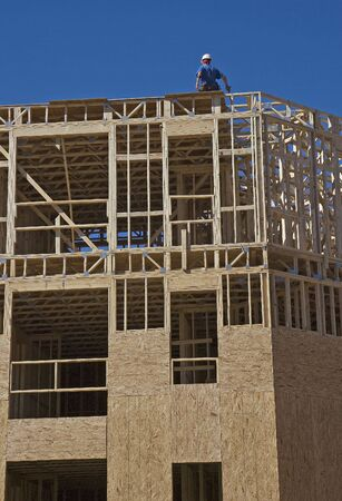 sheathing: A framer on a wood structure under construction
