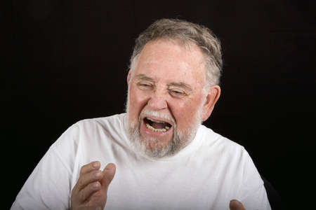 An older man in white tshirt on black background with an expression of pain or anguish