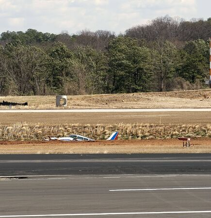 runways: A small aircraft in a ditch between two runways at an airport