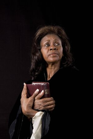 A black woman with a bible clutched to her chest eyes left photo