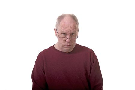 grouchy: An older bald man peering over the top of reading glasses on white background