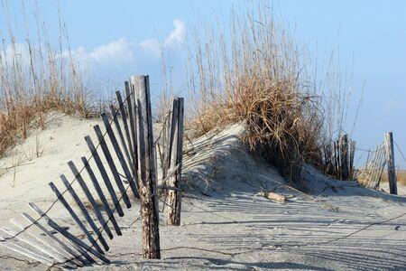 Een gebroken hek loopt door zandduinen en zee haver tegen een blauwe hemel