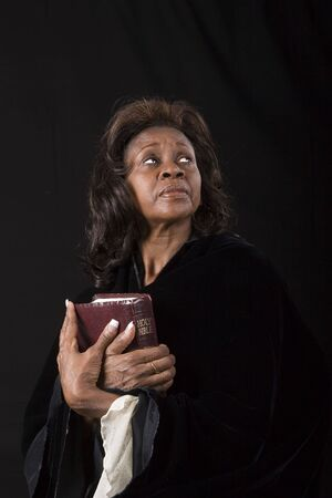 A black woman holding a bible with her eyes looking to heaven Imagens