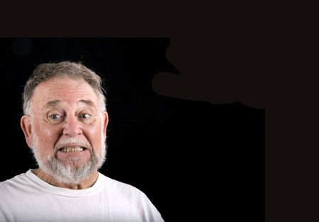 An old man in a white t-shirt on a black background looking embarrassed Stock Photo