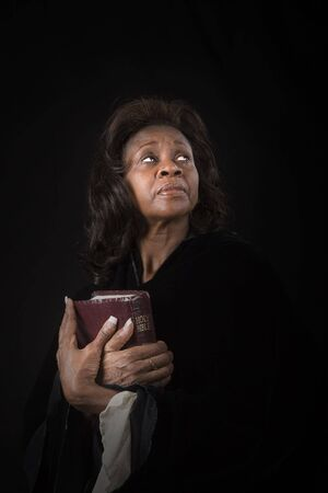 A black woman holding a bible with a heavenly light on her face Stock Photo - 2739161
