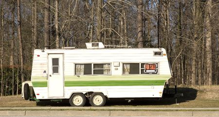 A yellow and green camper trailer on the side of the road with a for sale sign in the window