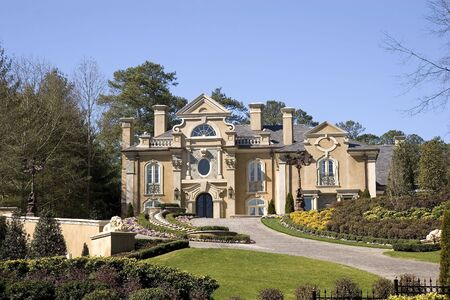 A large stucco mansion high on a manicured and landscaped lawn Stock Photo - 2752824