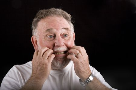 An old man with beard and mustache scratching his face with both hands