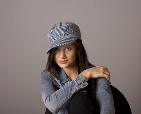 A young brunette woman in a denim jacket and cap with her hand on her shoulder sitting in a chair against a grey background Stock Photo - 2784340
