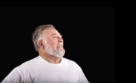 pained: An older man in a white t-shirt on black background with a grimace or pained expression
