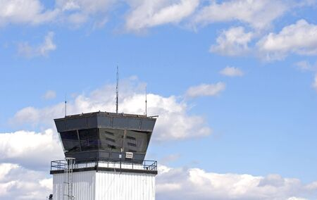 departing: An air traffic control tower at a small regional airport against a blue sky with white puffy clouds