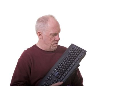 exasperated: An older man with a computer keyboard looking confused or exasperated