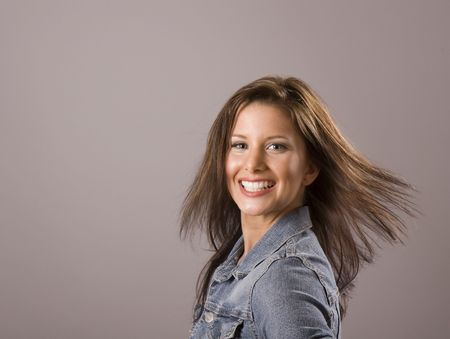 A brunette in denim jacket with hair flying in the breeze