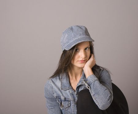 elbow chair: A brunette wearing a denim jacket and cap with her elbow resting on the back of her chair