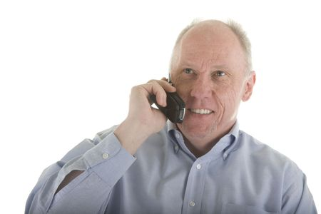 An older guy in a blue dress shirt talking on a cell phone and smiling Stock Photo - 2885516