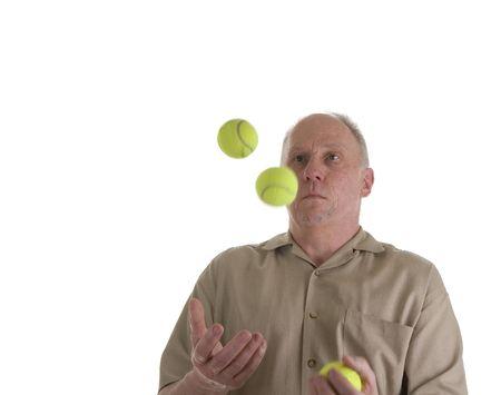 An older guy in a brown shirt juggling green tennis balls photo