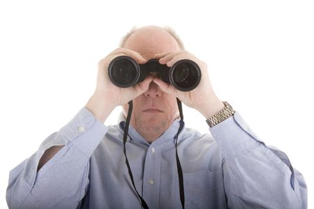 A man in a blue shirt looking directly at camera through binoculars