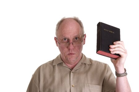 An older guy wearing a brown shirt and glasses holding a bible and looking at camera Фото со стока