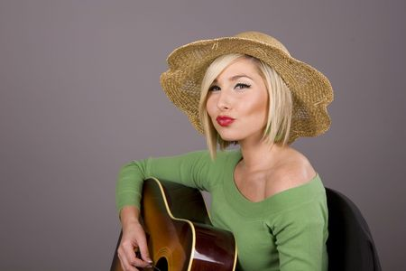 puckering lips: A blonde in a green blouse playing the guitar and puckering her lips
