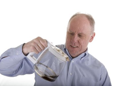 A man in a blue shirt looking at an almost empty coffee pot