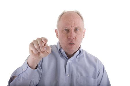 pissed: An angry man in a blue dress shirt looking mad and pointing at viewer Stock Photo