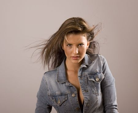 blown: A brunette with her denim jacket unbuttoned and hair blown across her face