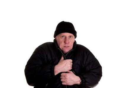 frigid: An old guy shivering cold in a heavy black coat and wool cap
