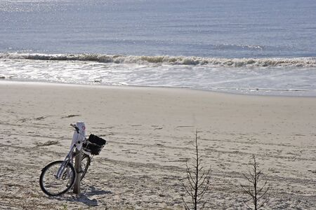 A lone bicycle on an empty stretch of beach photo