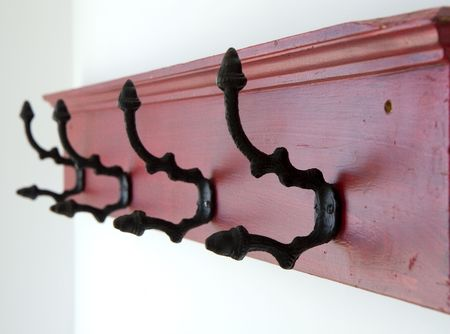 A colorful hat rack of black hooks on a red board