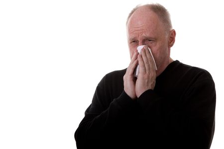 An older buy in black shirt on a white background blowing his nose into a tissue with a cold or the flu