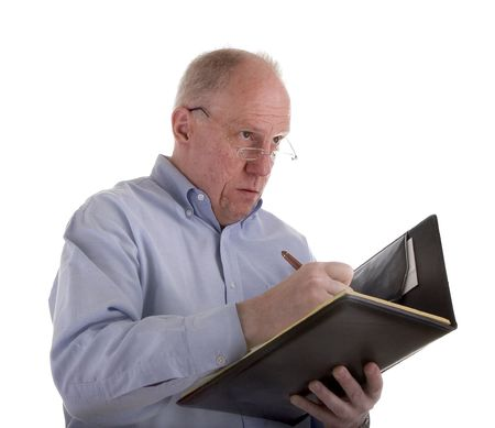 An older guy in a blue shirt writing an estimate or invoice