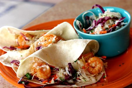 Three shrimp tacos and slaw on colorful plates Фото со стока