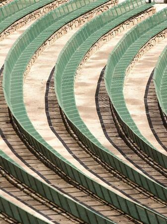 Rows of Semi-circular green amphitheater benches at a park