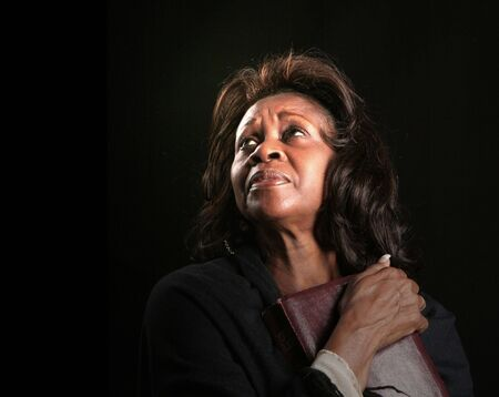 clutching: A spiritual black woman clutching her bible and looking toward heaven Stock Photo