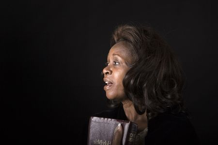 A black woman with bible in hand singing hymns