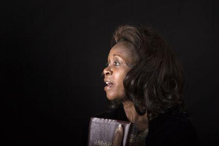 hymnal: Una donna nera con la bibbia in mano cantando inni
