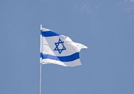 israeli: An Israeli flag blowing in the wind against a brilliant blue sky