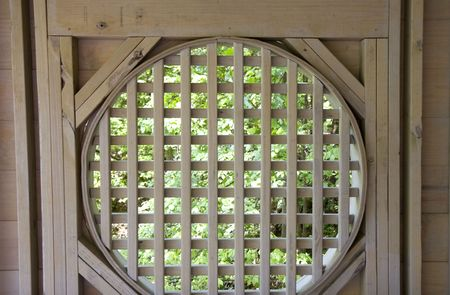 lattice window: A lush green forest shot through a wooden grid detail in a gazebo