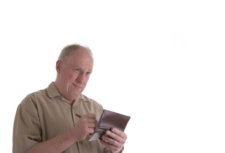An older buy with a brown shirt writing a check and looking upset or confused photo