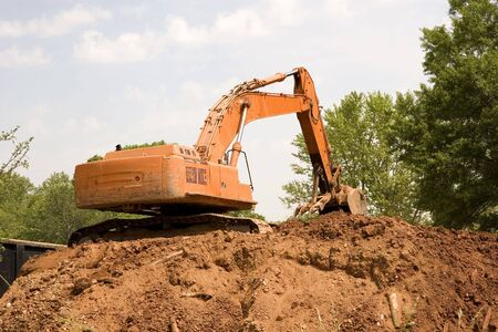 front end: An orange front end loader on a pile of dirt Stock Photo