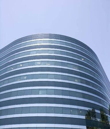 A modern curved blue glass building against a blue sky photo