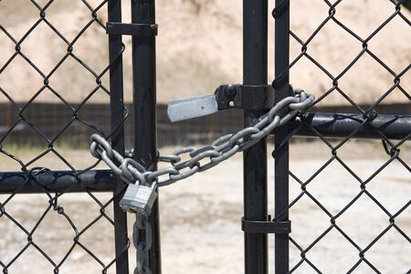 A silver lock and chain on a black chain link gate Stock Photo - 3146311