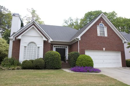 A nice brick house planted with purple flowers photo