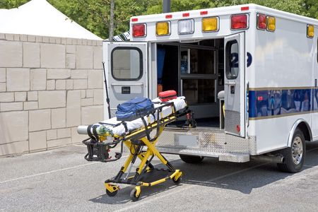 An ambulance in a parking lot with a gurney and medical emergency equipment