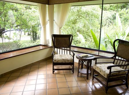 Enclosed glass patio at a luxury hotel in a jungle setting Stock Photo