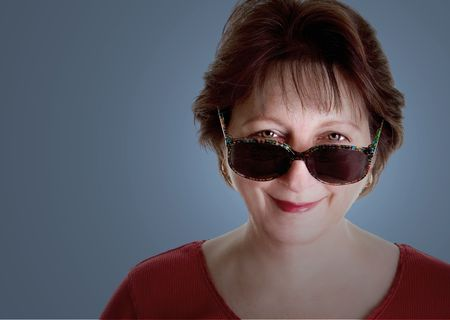 An attractive middle aged woman looking over her sunglasses photo