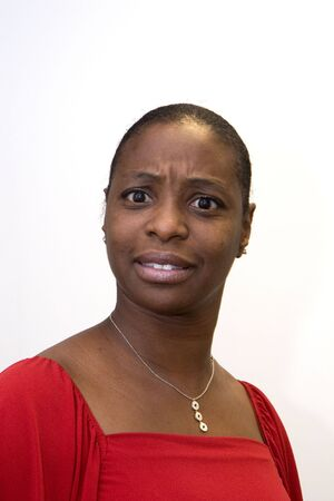 A black woman in a red dress with a confused look