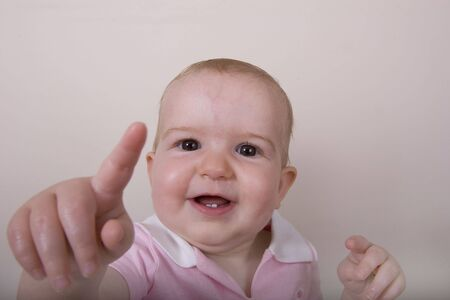 A baby in pink pointing toward the camera photo